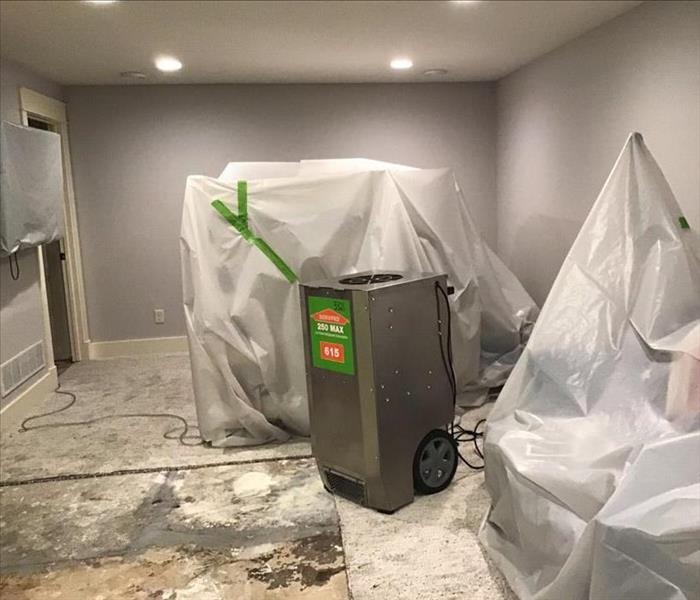 stainless steel dehumidifier in a water damaged room with plastic covering the furniture